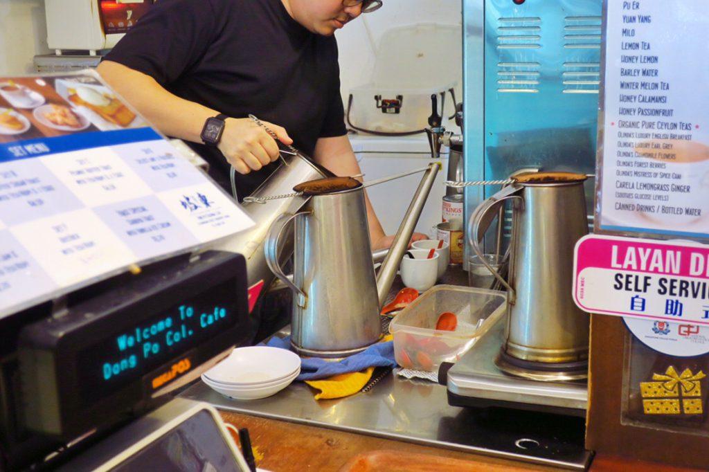 伝統的なコピを入れるドン・ポ・コロニアル・カフェの店主